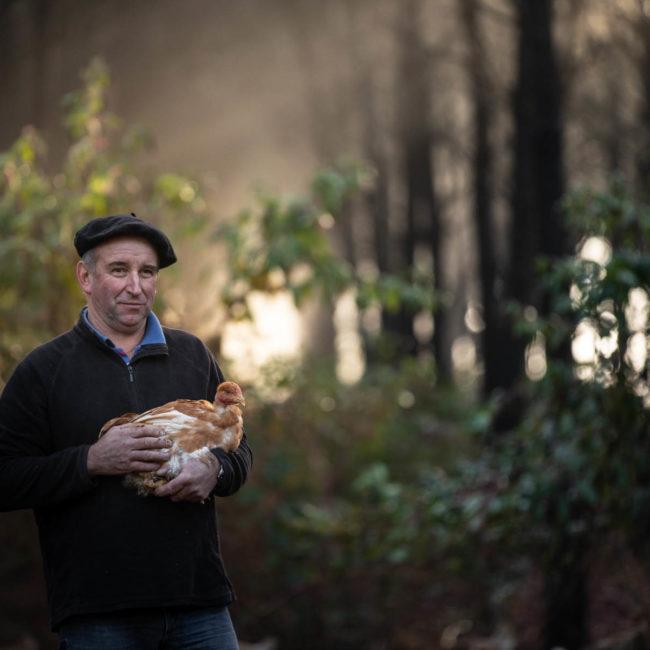 photo d'un fermier landais avec une poule dans les bras au milieu des pins par Carole photographe