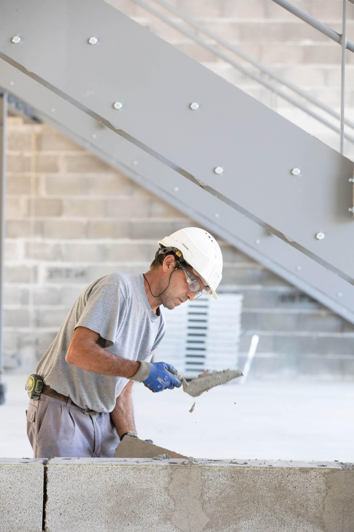 photo d'ouvrier qui travaille avec une truelle sur un chantier de construction par Carole photographe d'entreprise
