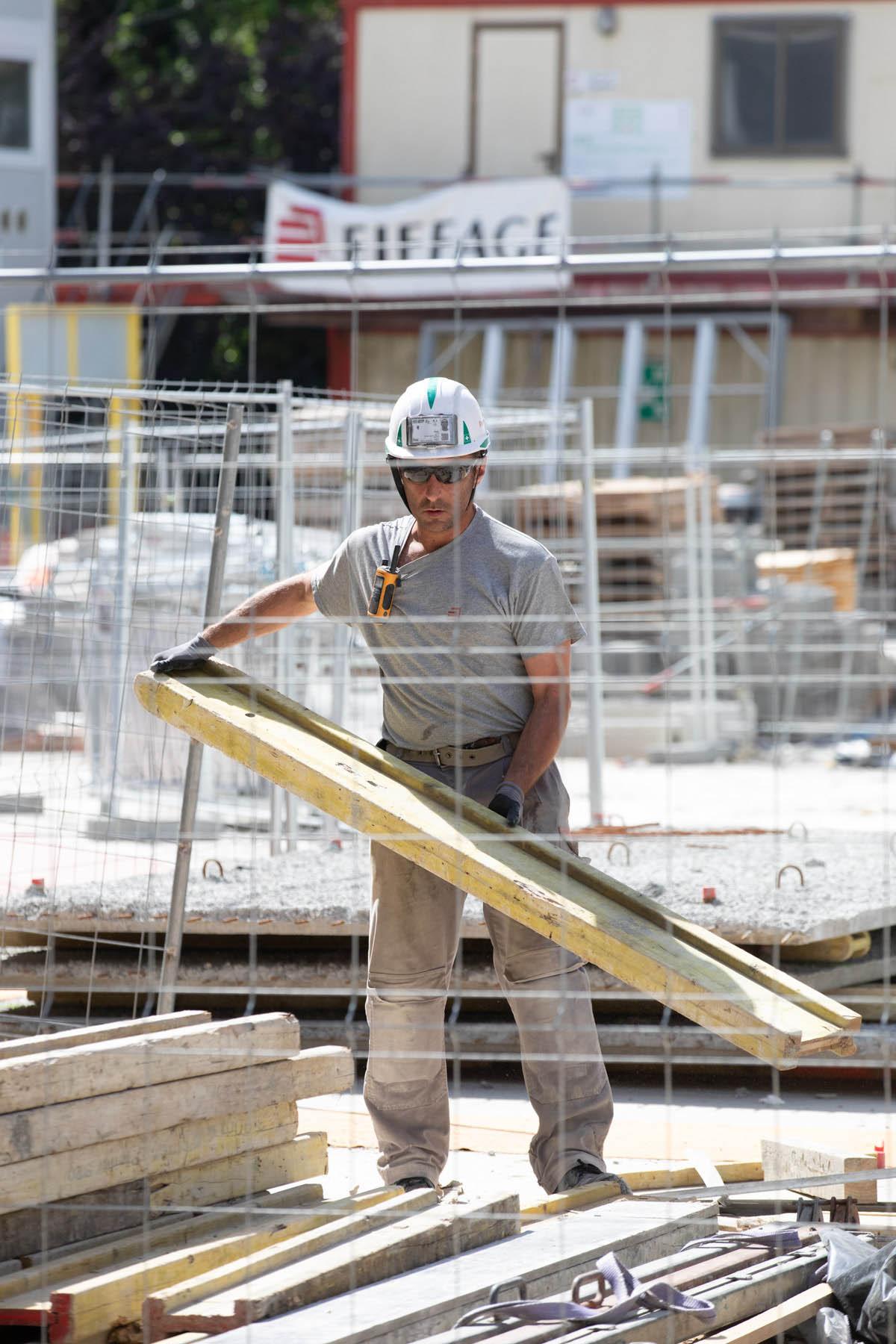 photo d'un ouvrier portant des planches sur un chantier de construction à bayonne par Carole photographe d'entreprise